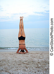 Yoga Near Sea - Svelte mature woman standing on her head...