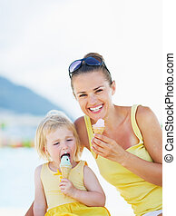 Smiling mother and baby eating ice cream
