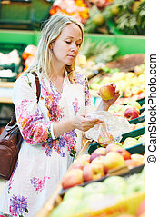 Young woman at food shopping in supermarket - Woman choosing...