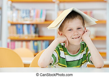 young boy with book in library