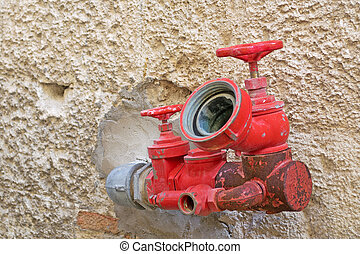 red spigot - red  hydrant faucet on a yellow wall