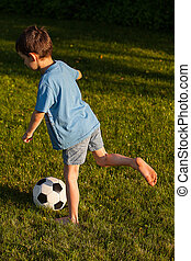 Young kicker - A young boy kicking a footbal on the grass