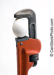 Pipe wrench with an egg in its jaws - pipe wrench with an...