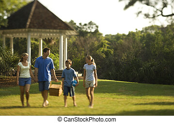 Family in park - Caucasian family of four carrying picnic...