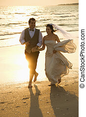 Bride and groom on beach - Caucasian mid-adult bride and...