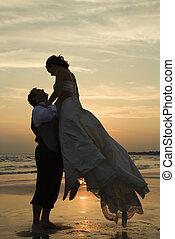 Groom lifting bride up. - Caucasian mid-adult groom lifting...