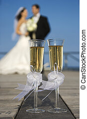 Bride and groom with champagne. - Pair of flute glasses of...