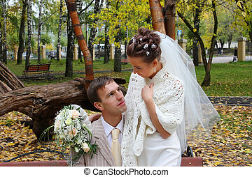 Happy bride and groom look at each other at bench in autumn park