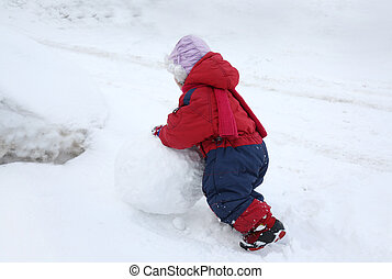 little girl rolling snowball - Back of little girl wearing...