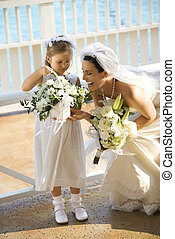 Bride and flowergirl. - Caucasian mid-adult bride kneeling...