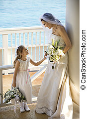 Bride and flowergirl. - Caucasian mid-adult bride holding...