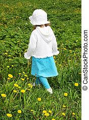 Back of little girl walking on green field