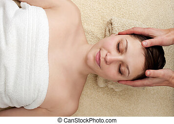 Young woman enjoying head massage at spa