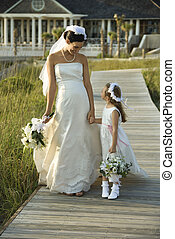 Bride and flower girl walking - Caucasian mid-adult bride...