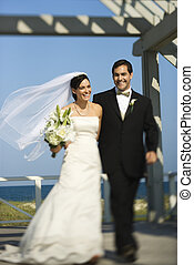Bride and groom walking - Caucasian mid-adult bride and...