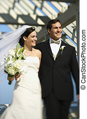 Bride and groom walking. - Caucasian mid-adult bride and...