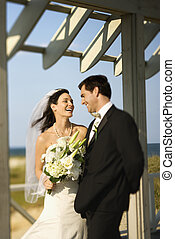 Bride and groom laughing - Caucasian mid-adult bride and...