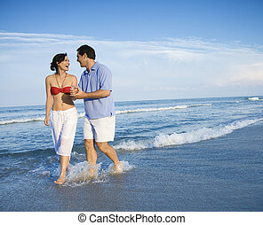 Couple walking on beach. - Caucasian mid-adult couple...