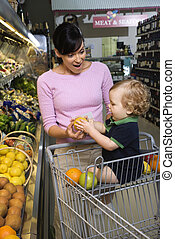 Mother grocery shopping with toddler. - Caucasian mid-adult...