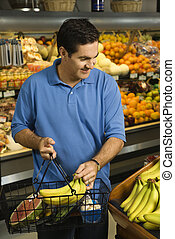 Man grocery shopping - Caucasian mid-adult male grocery...