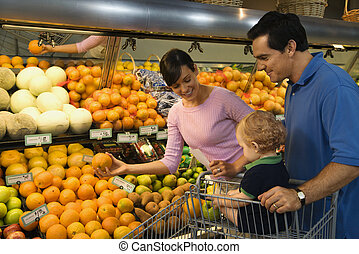 Family grocery shopping. - Caucasian mid-adult parents...
