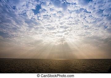 Sunbeam through the haze on the sky over the sea