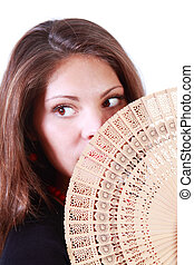 Young woman looks away and hides her mouth by fan isolated...