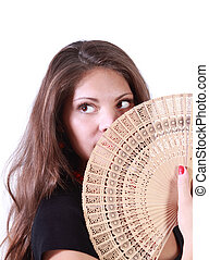 Young woman looks up and hides her mouth by fan isolated on...