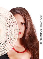 Beautiful girl looks at camera and half of her face by fan...