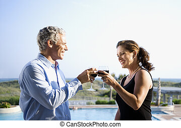 Couple toasting - Caucasian mid-adult couple making toast...