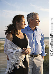 Couple at beach. - Caucasian mid-adult coulpe looking off to...