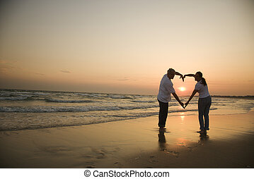 Couple in love. - Mid-adult couple making heart shape with...
