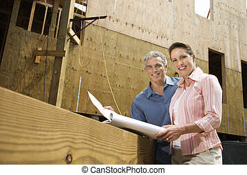 Man and woman reading blueprints. - Caucasian mid-adult male...