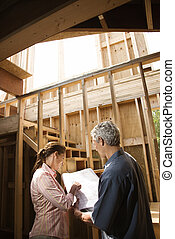 Couple looking at new house. - Caucasian mid-adult male and...