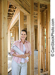 Woman on construction site. - Caucasian mid-adult female...