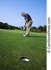 Man putting golf - Image of mid-adult male putting golf ball...