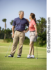 Couple talking on golf course - Caucasion mid-adult man and...