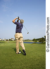 Man playing golf - Back view of Caucasion mid-adult man...