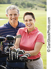 Couple on golf course - Caucasion mid-adult man and woman...