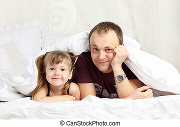 Little girl and her father look out from under blanket on bed