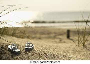Sandals on beach. - Two white sandals on sandy beach with...