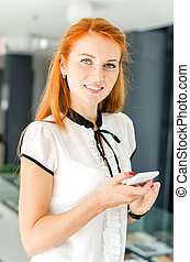 Young woman in modern interior using mobile phone