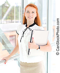 Pretty young woman with computer in modern interior