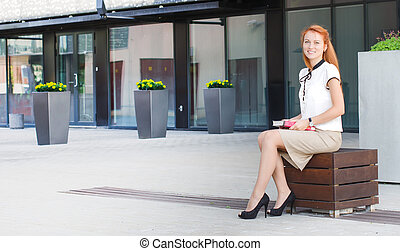 Female student sitting outdoors with book