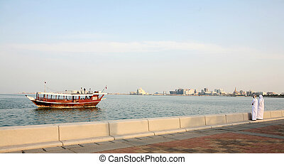 Doha Corniche locals and boat - Two Arab locals look out...