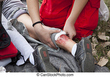 first aid training - Paramedic applying bandage to leg of an...