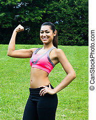 Young fit woman flexes her muscles