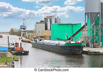 Ship in harbor of the cement plant. Netherlands