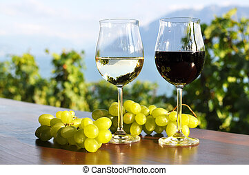 Two wineglasses and grapes against Geneva lake. Lavaux...