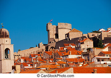 Main tower of Dubrovnik fort walls with town roofs on...